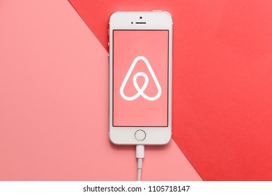 MINSK, BELARUS - May 11, 2018: Top view of white Apple Iphone with Airbnb logo on display. Flat lay with  smartphone on the pink and coral table as background.