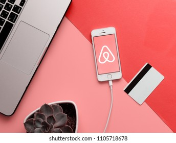 MINSK, BELARUS - May 11, 2018: Top view of white Apple Iphone with Airbnb logo on display. Flat lay with credit bank card, laptop, succulent plant and smartphone on the pink and coral table background