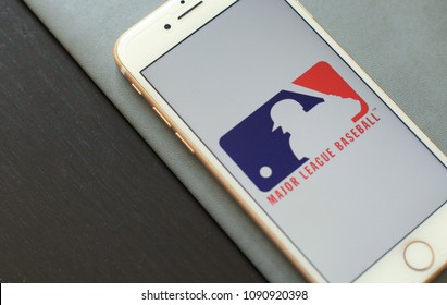 MINSK, BELARUS – May 12, 2018: White Apple iPhone 7. The official logo of the Major League Baseball, MLB logo.