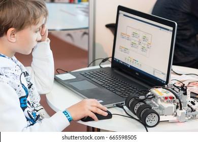 Minsk, Belarus. May, 2017. Exhibition of robots and modern technology. Modern robot. The teenager boy is programming Lego robot. Robotics. STEM education.