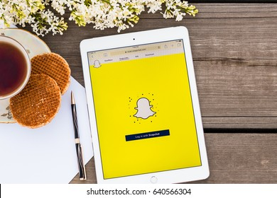 Minsk, Belarus - May, 2017: IPad Air Apple is on the old wooden table. Social networks icon Snapchat is on the screen, registration page. Lilac and a cap of tea and cookies.