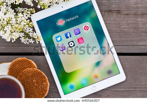 Minsk, Belarus - May, 2017: IPad Air Apple is on the old wooden table. Social networks icons Twitter, Facebook, Viber, Pinterest, Uber, Airbnb is on the screen. Lilac and a cap of tea and cookies.