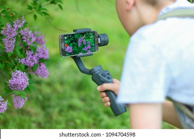 Minsk, Belarus - May, 2018: DJI Osmo Mobile 2. Steadicam. Samsung phone. Stabilizer for cell phone, smartphone. A teenager boy in the garden shoots beautifull lilac bushes for his YouTube chanel blog.
