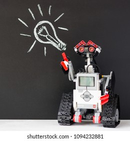 Minsk, Belarus - May, 2018: Lego robot. Robotics. School. Picture of a light bulb in the background. Concept. High intelligence. STEM education.