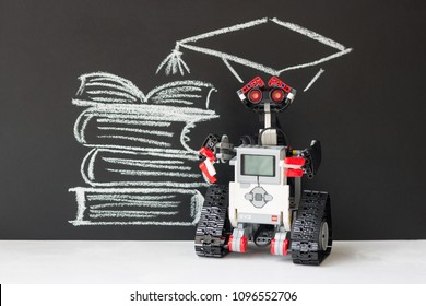Minsk, Belarus - May, 2018: Lego robot Mindstorms EV3. In the background, a stack of books is drawn on the blackboard, an academic cap over the head of the robot.