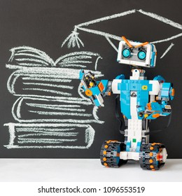 Minsk, Belarus - May, 2018: Lego Boost robot. In the background, a stack of books is drawn on the blackboard, an academic cap over the head of the robot.