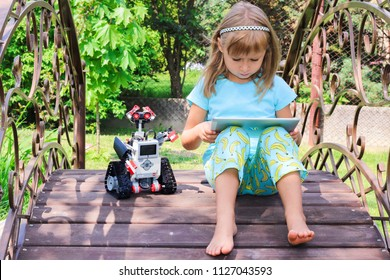 Minsk, Belarus - May, 2018: Little girl programs Lego robot Mindstorms EV3 on IPad Apple in summer Stem robotic camp. Elementary school in the garden. Robotic class. Lesson. AI. Code bot.