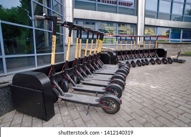 Minsk, Belarus - May 2019. Row of rental electric scooters parked on a street sidewalk. Electric scooters for rent. Urban transport for hire. Electric ride sharing scooters ready to rent.