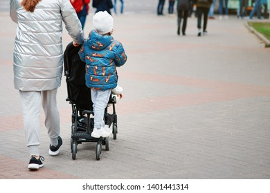 Minsk, Belarus - May 2019. Stroller extension, brother and sister share in walks. Sister comfortably travel in a standing position. Mom with children walking through the city with stroller.