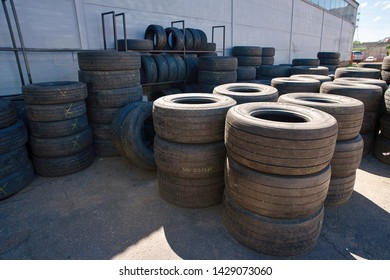 Minsk, Belarus - May 2019. Used car tyres pile in warehouse at repair shop. New and used tires stacked in outdoor warehouse, aqiting for instalation on trucks. Used lorry tires at tire shop.