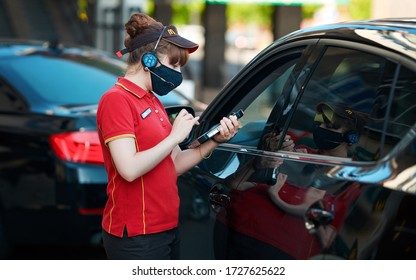 Minsk, Belarus. May 2020. Costumer ordering food from car on McDrive, McDonald`s fast food restaurant. McDonald's employee in protective mask takes orders with tablet at McDrive
