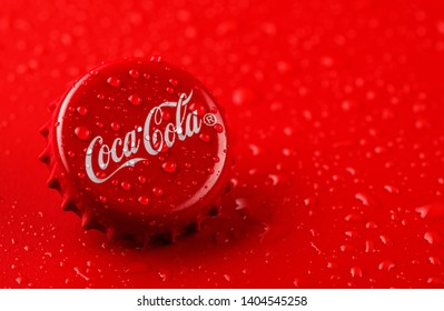 MINSK, BELARUS - MAY 21, 2019: Coca Cola Cap. Coca Cola Cap with drops on a red background