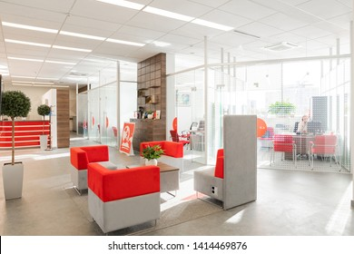 Minsk, Belarus - May 23, 2019: Corner of modern office with white walls, gray floor, open space area with red-white armchairs and rooms behind glass wall