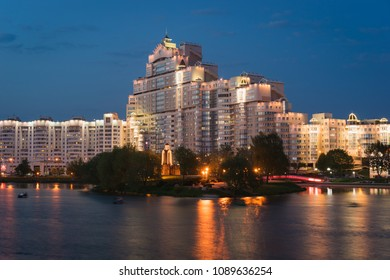 Minsk, Belarus - May 4 2018: Residential complex At Troitsky and Island of Tears Memorial illuminated in the evening. Svislach River embankment, Nemiga, Minsk City