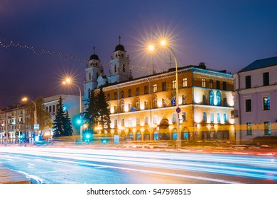 Minsk, Belarus. Night View Of Cathedral of Saint Virgin Mary And Building of French Embassy in Republic of Belarus. Traffic On Illuninated Pobedtiley Avenue Street In Minsk, Belarus.