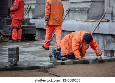 Minsk, Belarus - Nov 2018. Worker putting down paving slub during construction of city street. Brick paving works. Bricklayer places concrete paving stone for building up  footpath. Making sidewalk