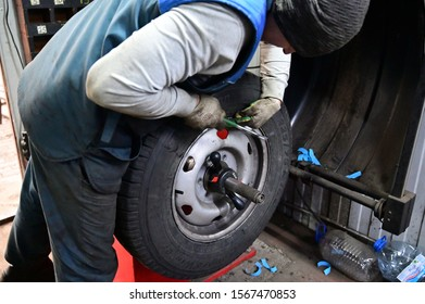 Minsk, Belarus - November 19, 2019: Photography with a tire fitting. A worker is serving a car. Balances the tire using a special machine and tool.