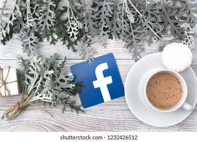 Minsk, Belarus. November, 2018. Facebook social network logo. Cineraria leaves, vanilla and cinnamon, a cup of coffee.