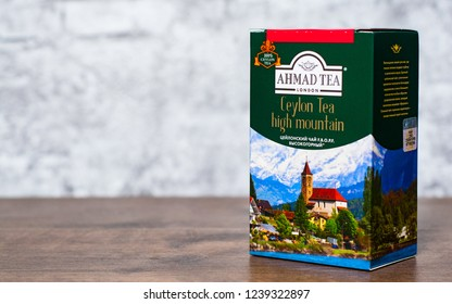 Minsk, Belarus - November 24, 2018: Box of Ceylon Ahmad Tea on wooden table on gray wall background with copy space