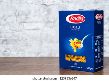 Minsk, Belarus - November 24, 2018: Barilla fusilli Italian pasta in a box on wooden table on gray wall background with copy space