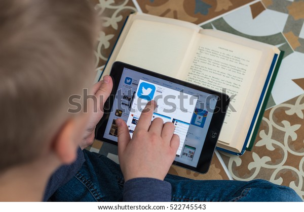 Minsk, Belarus - November 25, 2016: Boy teenager sitting in the lotus position on the floor and installs a program of the social network Twitter on iPad Apple from iTunes.