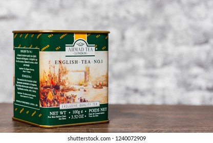 Minsk, Belarus - November 25, 2018: metal can Box of English Ahmad Tea on wooden table on gray wall background with copy space