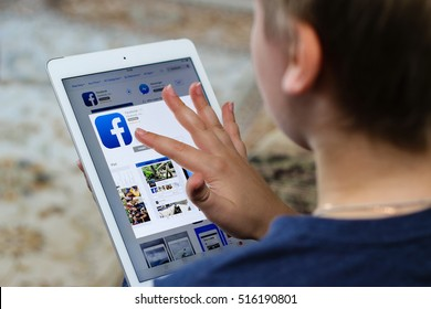 Minsk, Belarus - November 6, 2016: Boy teenager installs a program of the social network Facebook on iPad Air Apple from iTunes.