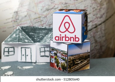 Minsk, Belarus - November 9, 2016: Travel around the world with Airbnb. Origami Paper  house. Logo Airbnb and globe.