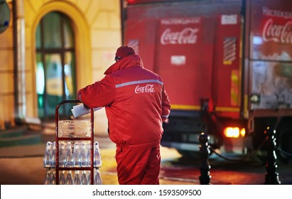 Minsk, Belarus. Oct 2019. Man with trolley full off bottles make delivery of beverages to restaurants. Coca-cola branded lorry on background. Coca cola man in uniform deliver soft drinks to customers