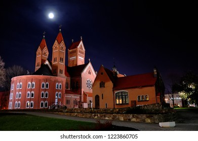 Minsk. Belarus - Oct.2010. Night view of Red Church of Saints Simon and Helena with moon in the sky. Neo-Romanesque architectural style. Roman Catholic church. View from the back.