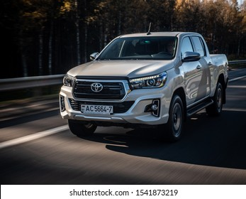 MINSK, BELARUS - October 17, 2019: Pearl white Toyota Hilux 2.8 D-4D drives on a highway during bright sunny day.