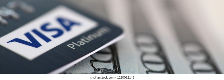 MINSK, BELARUS - October 19,2018: Embossed chipped VISA Platinum credit card and hundred dollar bank notes lying on silver keyboard closeup