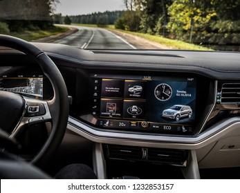 MINSK, BELARUS - OCTOBER 2, 2018: Advanced multimedia and infotainment system of the third generation of Volkswagen Touareg with 15-inch touch screen. View on a road through a windscreen.