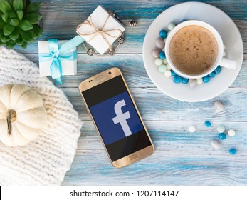 Minsk, Belarus. October, 2018. Smartphone with Facebook logo and page. A cup of coffee and colored candies, jewelry boxes, a bracelet with silver charms, succulent and a white decorative pumpkin.