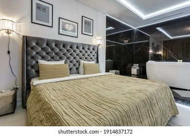 MINSK, BELARUS - OCTOBER 2020: Interior of modern luxury guestroom in studio apartments or hotel with big double bed, sofa, table, armchairs, bath and led light