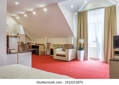 MINSK, BELARUS - OCTOBER 2020: Interior of the modern mansard guestroom in studio apartments or hotel with sofa table armchairs red carpet and led light
