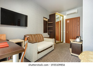 MINSK, BELARUS - OCTOBER 2020: Interior of the modern guestroom in studio apartments or hotel with sofa table armchairs red carpet and led light