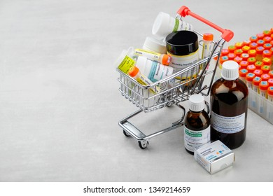 Minsk, Belarus - Oktober 26, 2019: Mini shopping cart full of homeopathic remedies and first aid kit with different homeopathic preparation. Concept of buying homeopathic drugs.