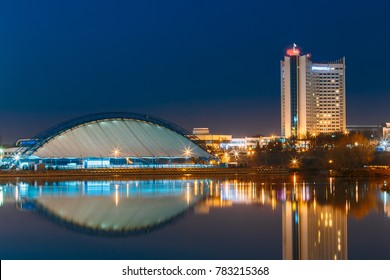 Minsk, Belarus. Old Soviet Hotel Building In Central Part Minsk, Downtown Nemiga. View With Water Reflections In Svisloch River. Night Scene Street