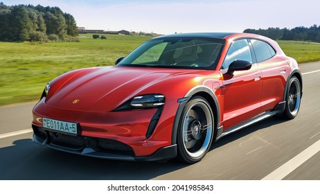 Minsk, Belarus - September 10, 2021: all-electric bright red Porsche Taycan Turbo Sport Turismo drives on a highway during a sunny day.