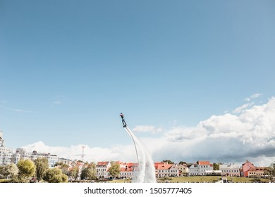 Minsk, Belarus - September 14, 2019: Flyboarder over the surface of the river against the background of the old city