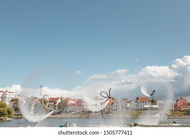 Minsk, Belarus - September 14, 2019: Three flyboarders synchronously do back flips above the surface of the river