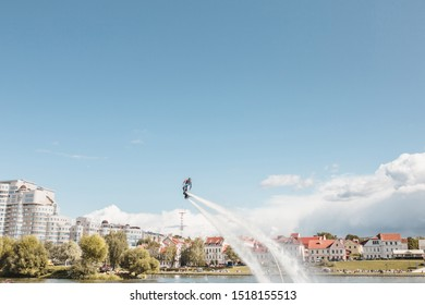 Minsk, Belarus - September 14, 2019: On a sunny day, a flyboarder trains and performs over the water area of the city