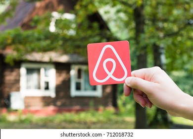 Minsk, Belarus - September, 2017: Travel around the world with Airbnb. Logo Airbnb and the old beautiful house with green garden on the background.