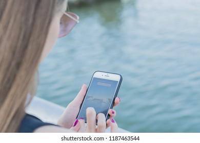 MINSK, BELARUS - September 21, 2018. Hand of woman using smartphone in park. Message type
