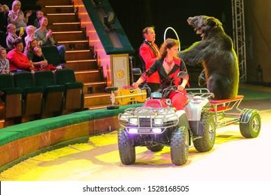 Minsk, Belarus - September 27, 2019: Trainer. Bear on a motorcycle. Russia. Bear on a bike. II Minsk International Circus Art Festival.