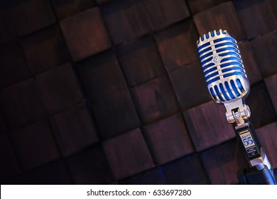 MINSK, BELARUS - SEPTEMBER 29, 2015: Vintage retro  microphone- SHURE Super 55 Deluxe against wood background. Karaoke, vocal learning, music shop or radio concept. Retro style mic ready to rock