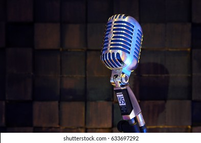 MINSK, BELARUS - SEPTEMBER 29, 2015: Silver old fashioned stage microphone- SHURE Super 55 Deluxe against wood background. Room for sound recording concept.