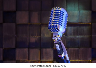 MINSK, BELARUS - SEPTEMBER 29, 2015: Silver old fashioned stage microphone- SHURE Super 55 Deluxe against wood background. Voice recording concept Retro style mic ready to rock