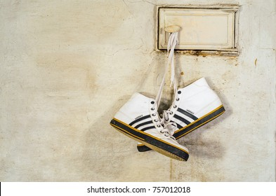 Minsk, Belarus - September 29, 2017: White Adidas Sneakers Hang on Laces and Dry on a Russian Stove, Close-up
